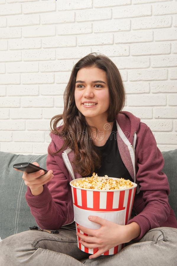 Teen girl sitting on couch with TV remote and eating popcorn stock images