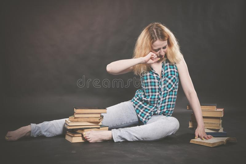 Teen girl sitting on the floor next to books and emotionally showing her hatred, hate and fatigue. Alone royalty free stock photo