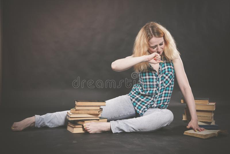 Teen girl sitting on the floor next to books and emotionally showing her hatred, hate and fatigue. Alone royalty free stock images