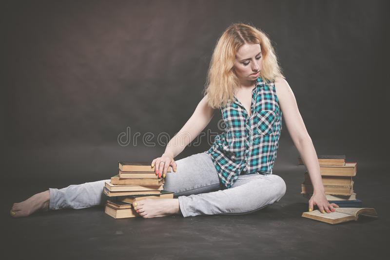 Teen girl sitting on the floor next to books and emotionally showing her hatred, hate and fatigue. Alone stock images