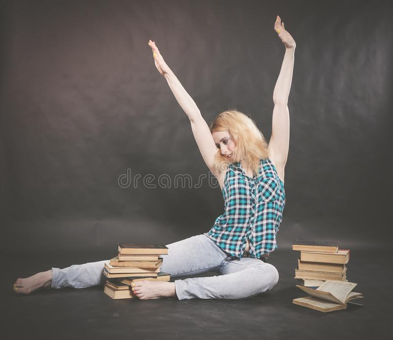 Teen girl sitting on the floor next to books and emotionally showing her hatred, hate and fatigue. Alone stock photos