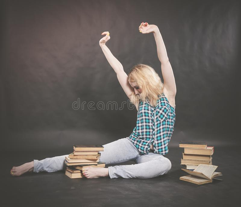 Teen girl sitting on the floor next to books and emotionally showing her hatred, hate and fatigue. Alone royalty free stock photos