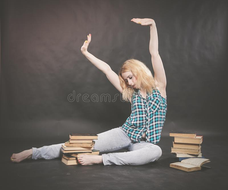 Teen girl sitting on the floor next to books and emotionally showing her hatred, hate and fatigue. Alone stock photo