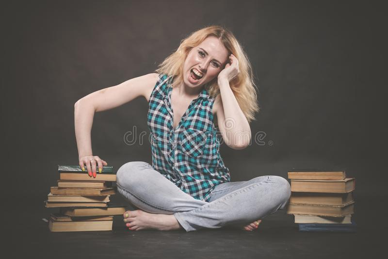 Teen girl sitting on the floor next to books and emotionally showing her hatred, hate and fatigue. Alone royalty free stock photography