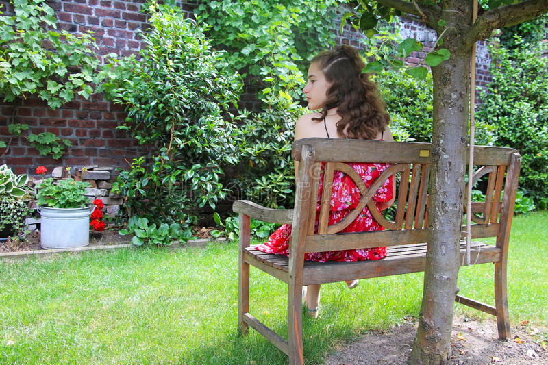 A teen girl sitting in the garden royalty free stock photo