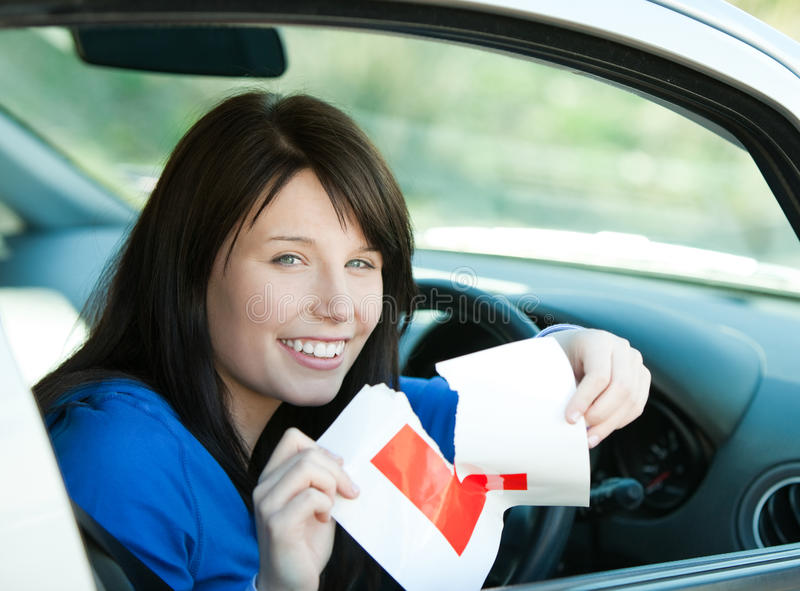Teen girl sitting in her car tearing a L-sign stock image