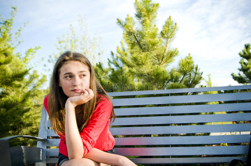 Teen girl sitting outside concerned thinking royalty free stock photography