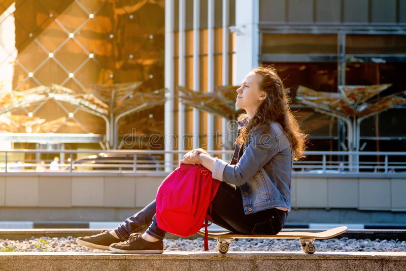teen girl sitting on a skate Board with a pink backpack in the big city stock photos