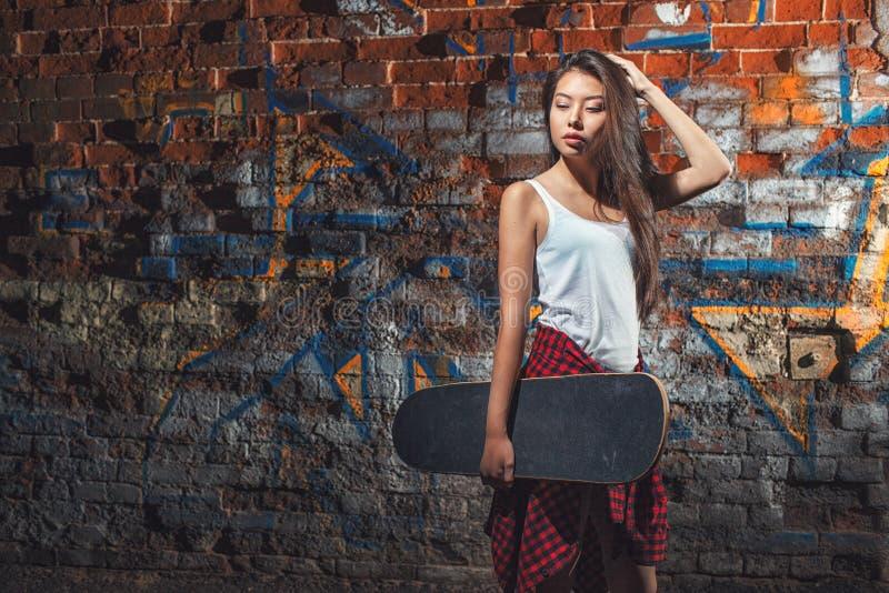 Teen girl with skate board, urban lifestyle. stock photo