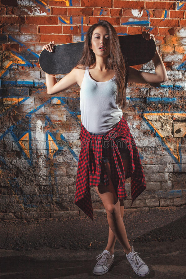 Teen girl with skate boardrs, urban lifestyle. Beautiful asian teen girl with skate board on shouldres. Outdoors, urban lifestyle royalty free stock photography