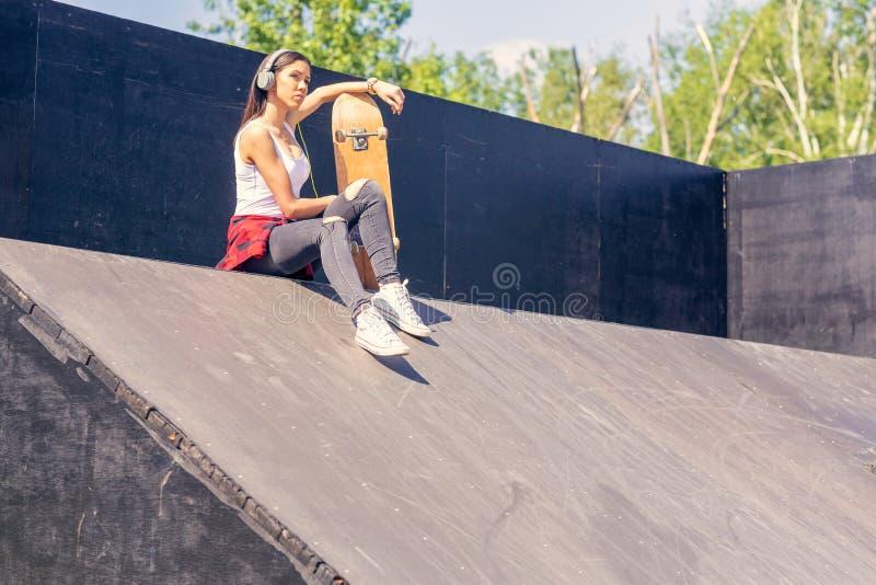 Teen girl with skateboard listening music. Outdoors, urban lifestyle. Cute teen girl with skateboard listening music. Outdoors, urban lifestyle royalty free stock image