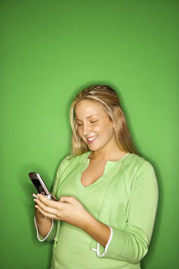 Teen girl smiling at cellphone. Portrait of blond Caucasian teen girl smiling at cellphone against green background stock photo