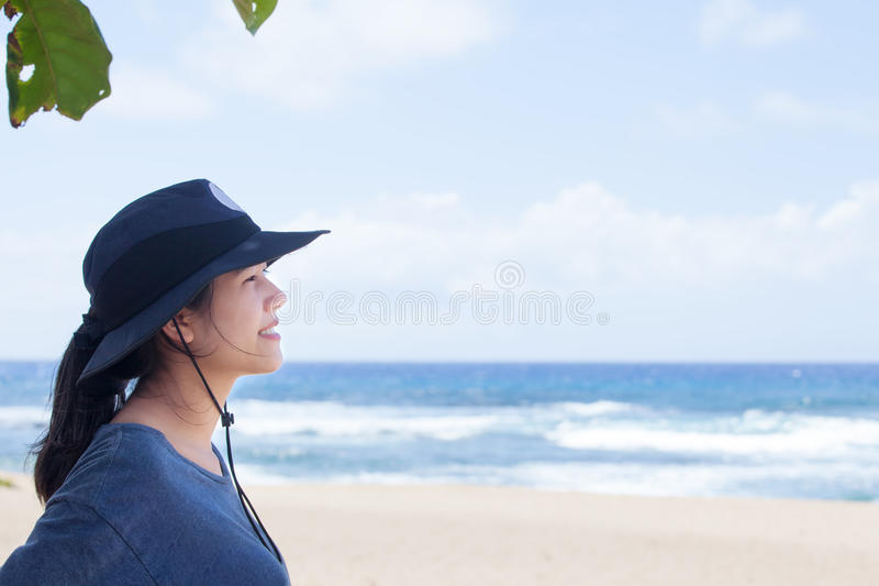 Teen girl smiling, looking out over ocean, side profile stock photography