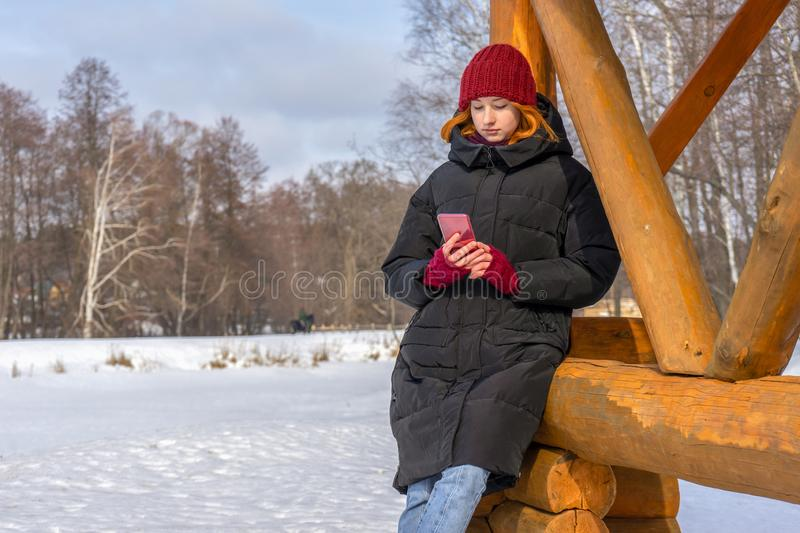 Teen girl spending time at countryside in winter. Young lady wearing fashion clothes standing near wooden arbor against landscape royalty free stock photography