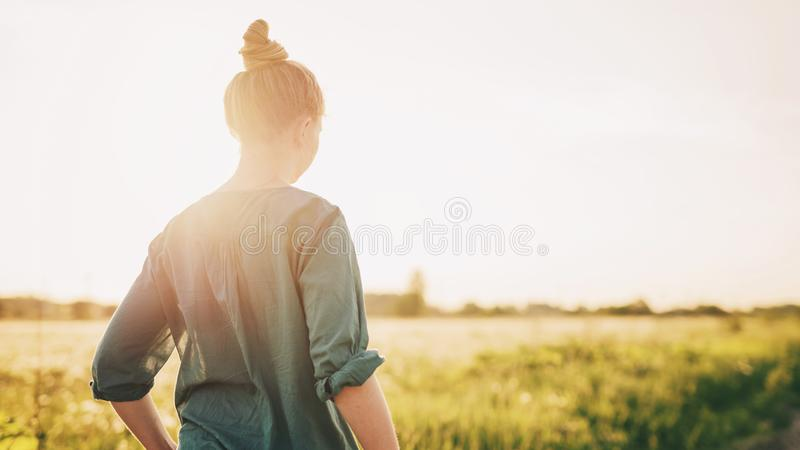 Teen girl stand on rural road shot from back stock image