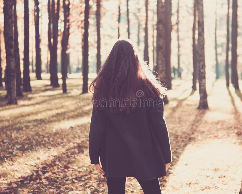 teen girl standing in the autumn Park with her back to the camera, turns on the spot. Woman with long hair standing outdoors royalty free stock images