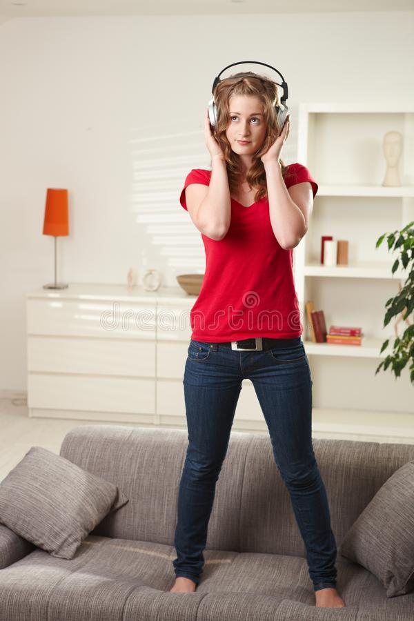 Teen girl standing on couch with headphones royalty free stock images