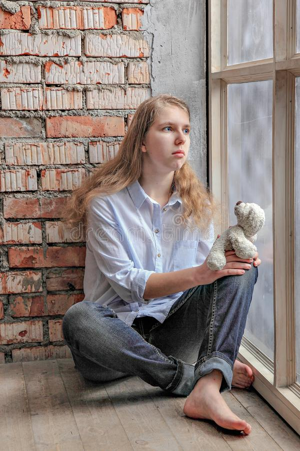 Teen girl standing at the window with a bear. sad lonely child. Problems of education of teenagers. stock image