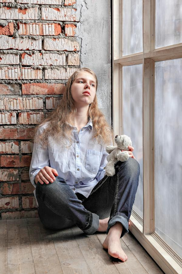Teen girl standing at the window with a bear. sad lonely child. Problems of education of teenagers. royalty free stock image