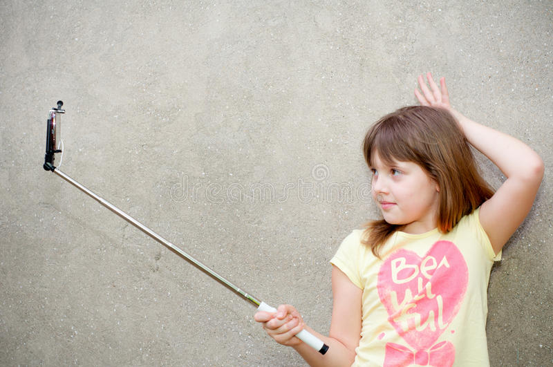 Teen girl stands with monopod in hands royalty free stock photo