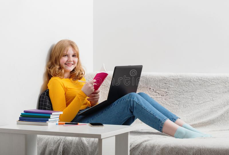 Teen girl learning with notebook at home. Online education,e-learning royalty free stock photos