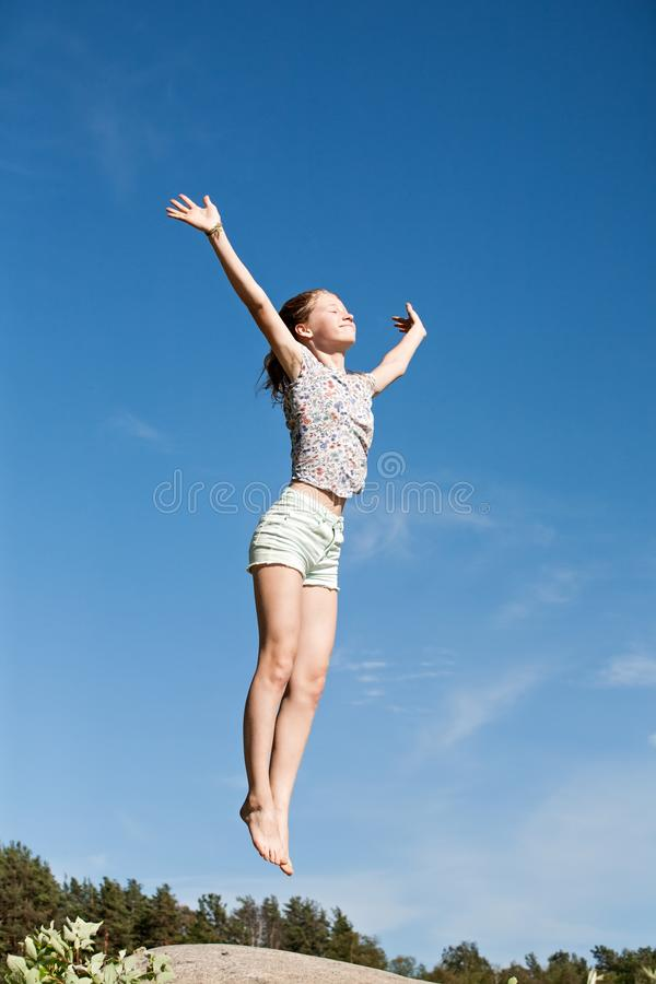 Teen girl happily jumping with her arms up on blue sky background royalty free stock images