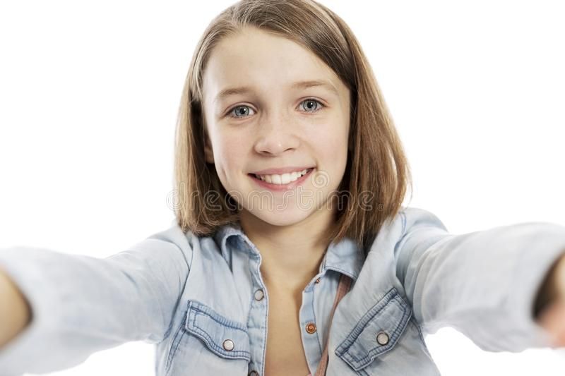 Teen girl takes pictures of herself, close-up. Isolated on a white background royalty free stock images