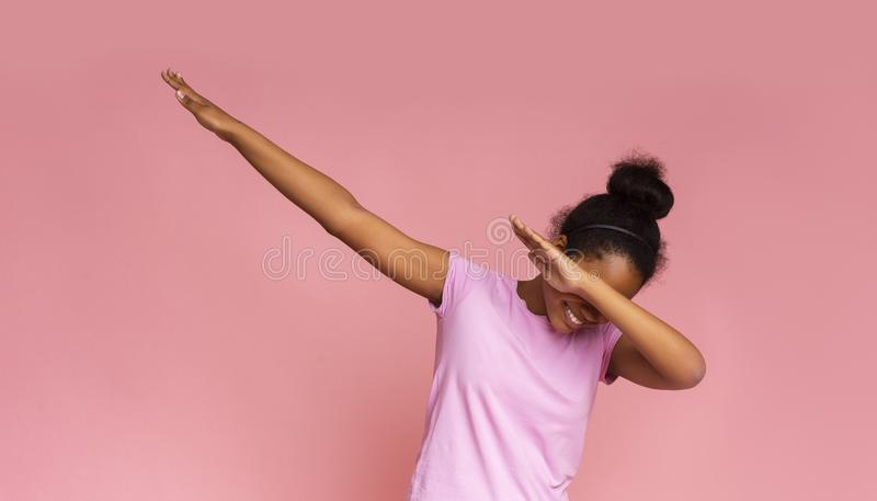 Teen girl throwing dab move standing against pink background. Panorama with copy space stock photos