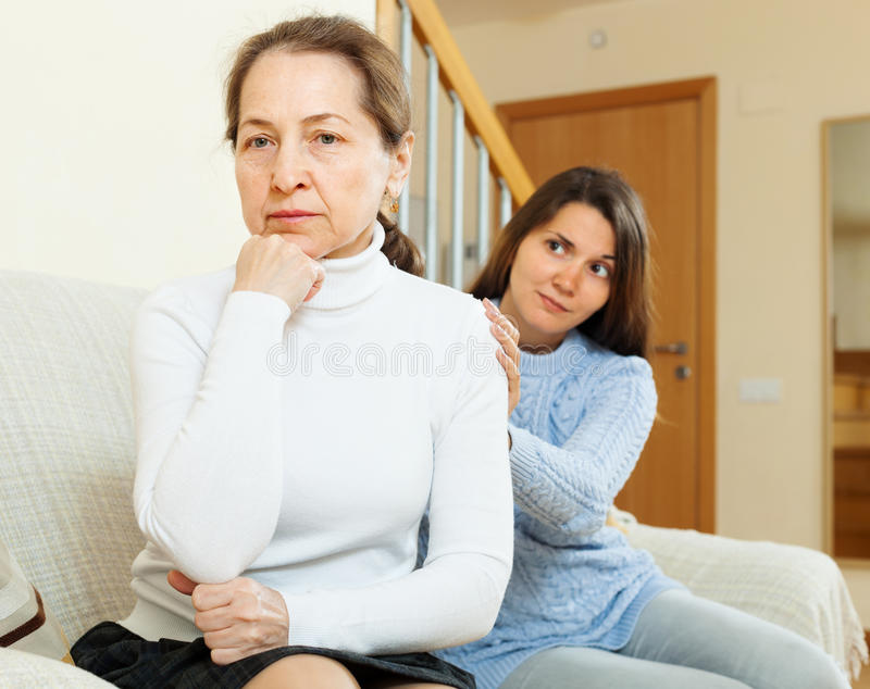 Teen girl tries reconcile with her mother. In home. Focus on mature stock photos