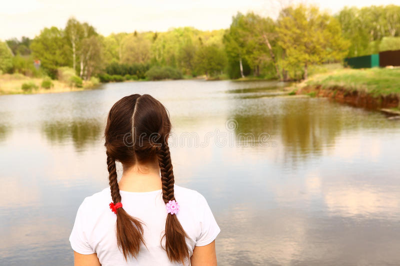 Teen girl turned back look on the summer lake stock photo