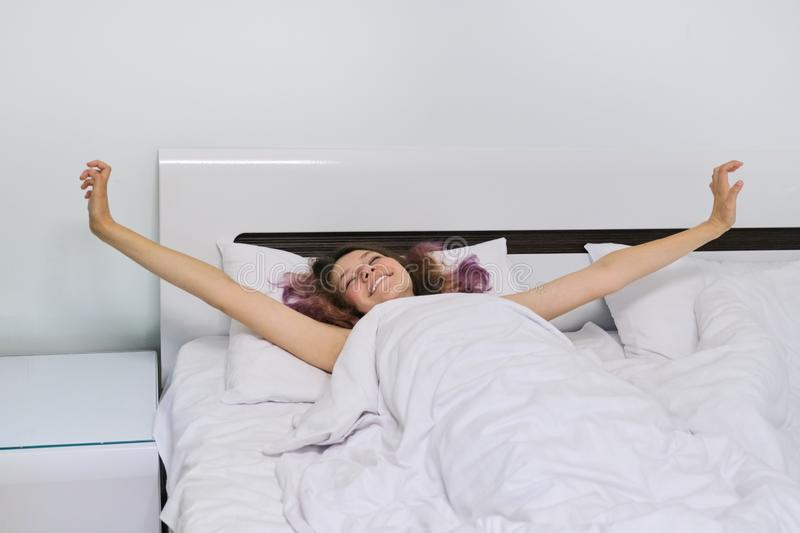 Teen girl waking up in the morning lying on pillow in bed with arms open stock photo
