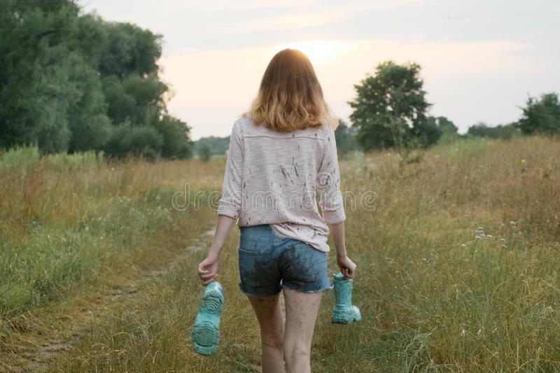 Teen girl walking on rural road with boots in hands royalty free stock photos