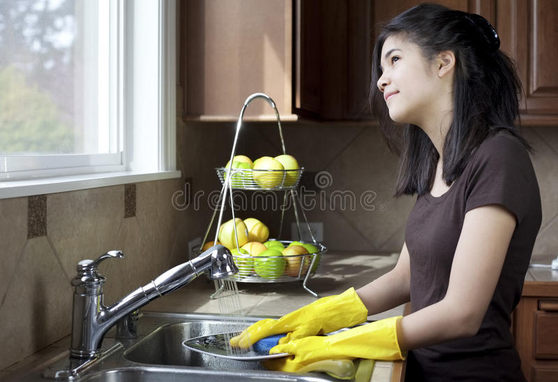 Teen Girl Washing Dishes At Kitchen Sink Stock Photo