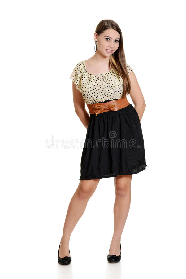 Teen girl wearing black and polka dot dress. On white background royalty free stock photo
