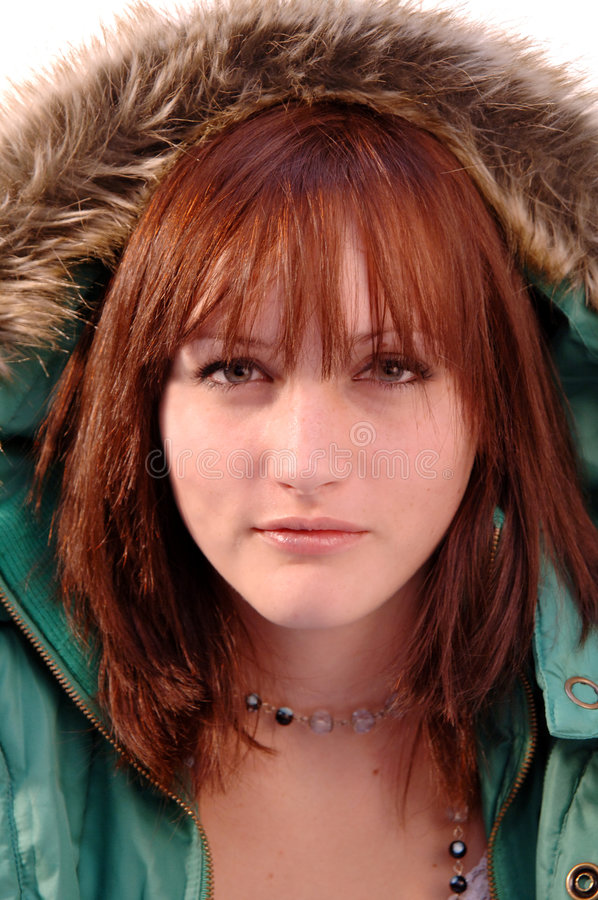 Teen girl wearing winter coat. A portrait of a pretty teenage girl with red hair, wearing a green winter coat with a hood pulled over her head stock images