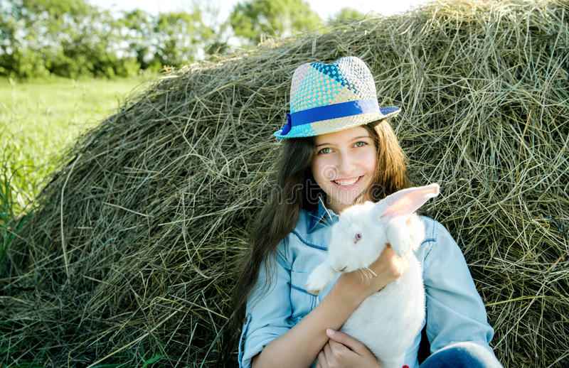 Teen girl with white rabbit sitting in front of haystack stock photo