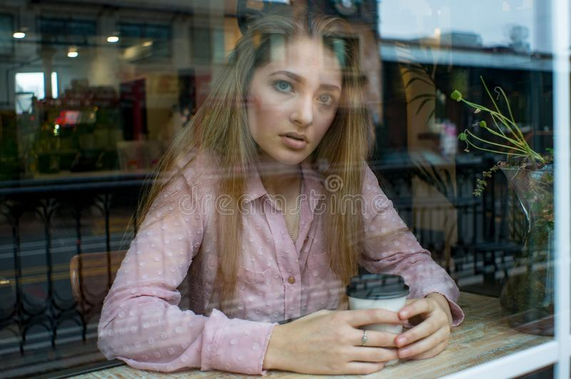 Teen girl in a window looking at camera stock photography