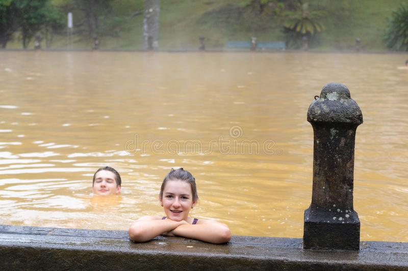 Teen girl and young adult man swimming and having good time in a mineral thermal pool in Terra Nostra park, Azores stock images