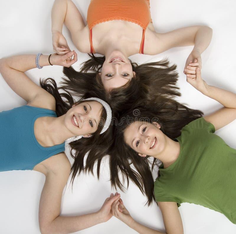Teen girls having fun. 3 teen girls lying on floor royalty free stock photos