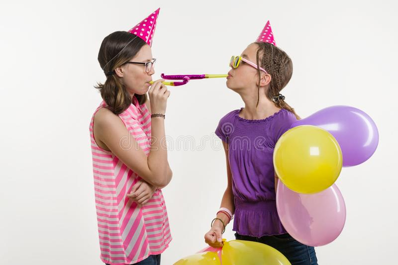 Teen girls at a party. Girls on a white background, in festive hats, blowing in the pipes. Teen girls at a party. Girls on a white background, in festive hats stock photos