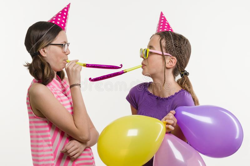 Teen girls at a party. Girls on a white background, in festive hats, blowing in the pipes. Teen girls at a party. Girls on a white background, in festive hats stock image