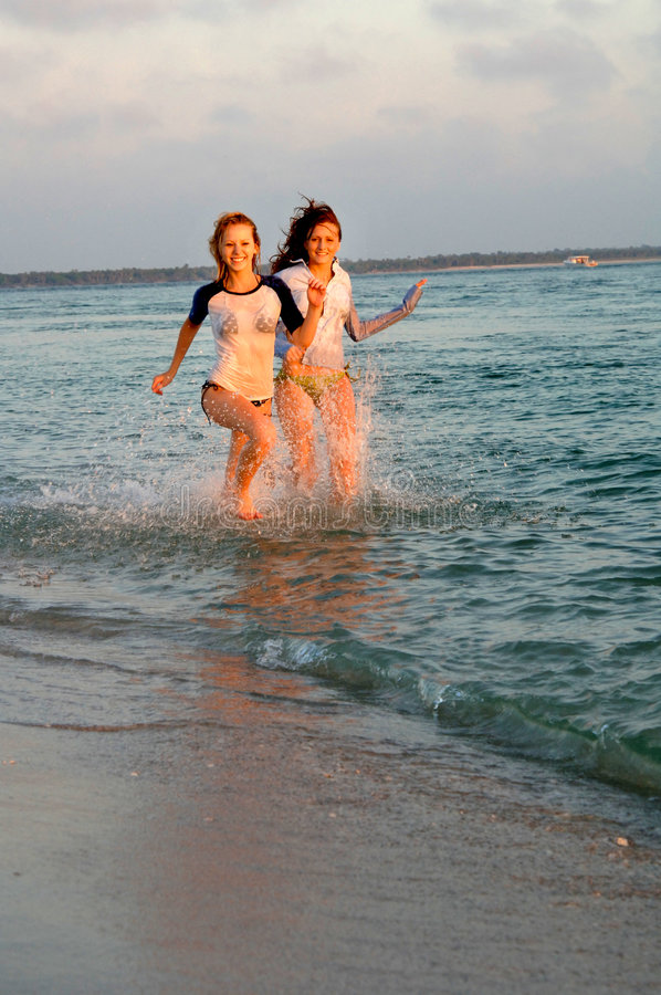 Teen girls running at beach royalty free stock images