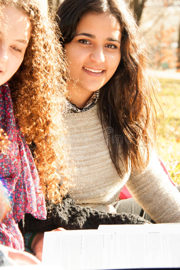 Teen girls studying outdoors stock photography