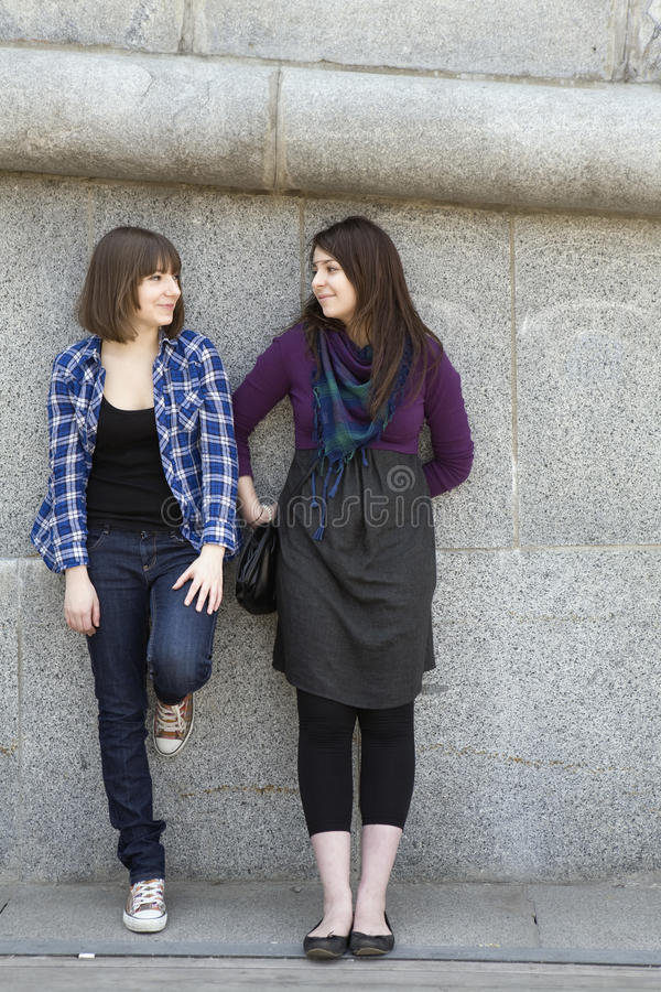 Teen girls talking at stone wall. Two teen girls talking at stone wall royalty free stock images