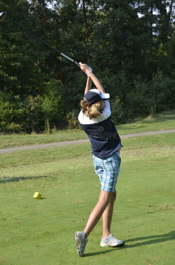 Teen golfer hits a golf ball  during a golf match royalty free stock photos