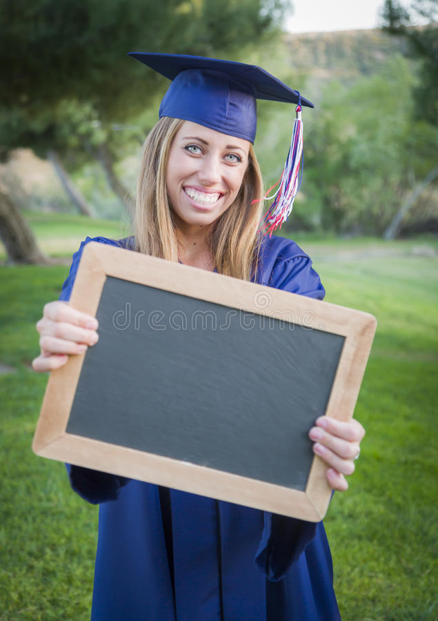 Teen Graduate with Blank Chalkboard Wearing Cap and Gown royalty free stock photos