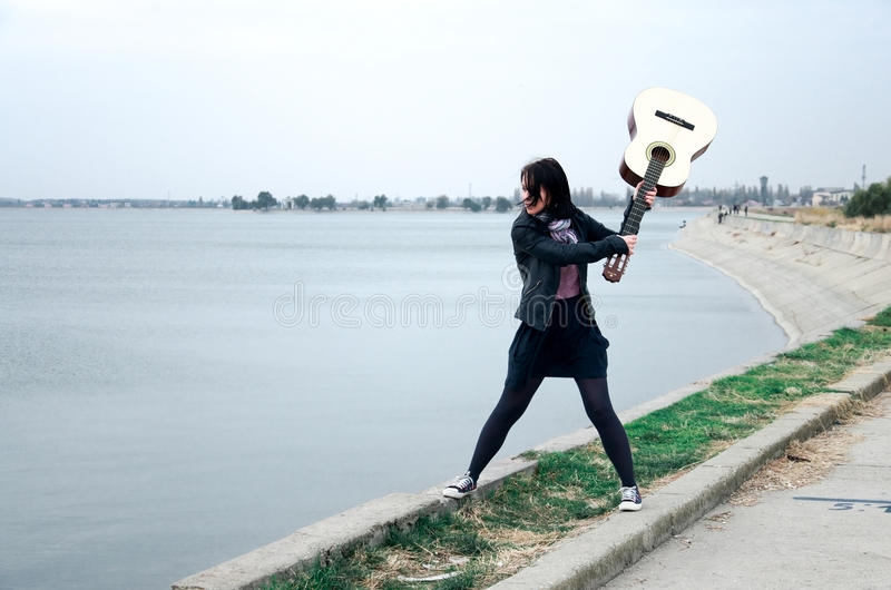 Teen with guitar. Teen trying to throw a guitar in the lake stock image