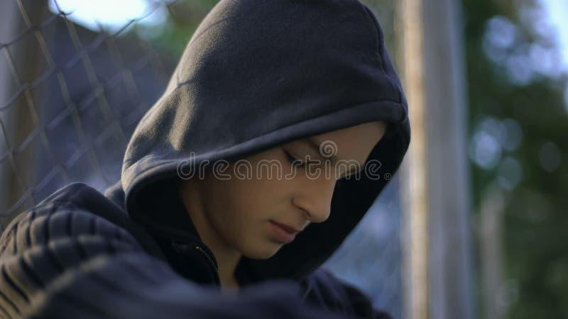 Teen guy feeling himself helpless, upset with bullying, hiding on backyard stock photography