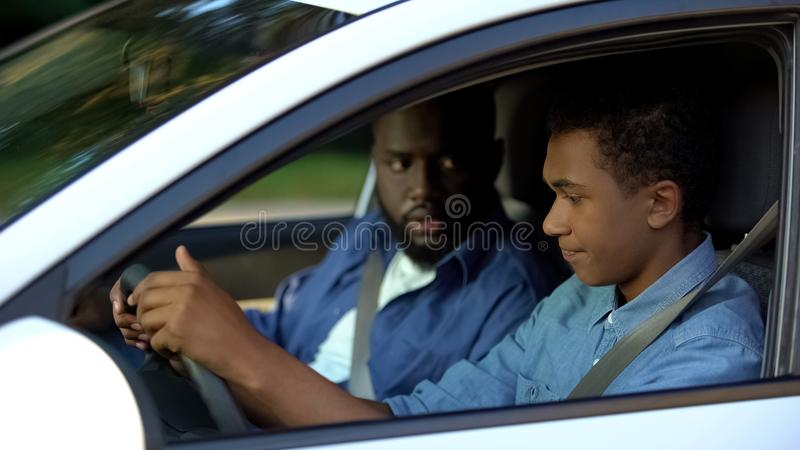 Teen guy feeling upset of driving, dad angrily looking at son, misunderstanding royalty free stock photos