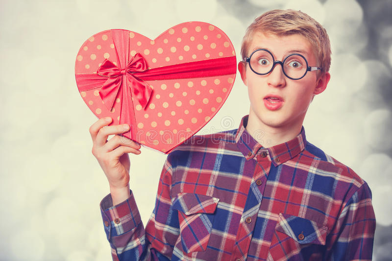 Teen guy with gift. Nerd teen guy with red heart shape gift royalty free stock photography